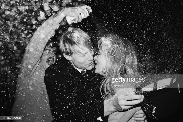 A police officer embraces a young woman holding his custodian helmet in his hand as second man sprays them with fake snow from a spray can during the...
