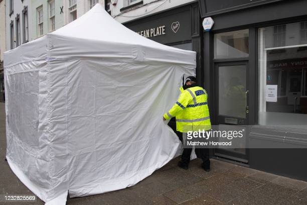 Police officer enters a police tent at the front of the Clean Plate cafe on Southgate Street on May 11, 2021 in Gloucester, England. Police search...