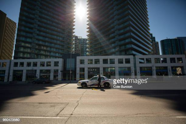 A police officer enters his police car at the cordoned off Yonge St at Finch Ave after a van plowed into pedestrians on April 23 2018 in Toronto...