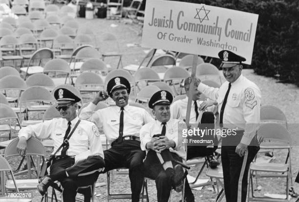 A police officer entertains his colleagues with a 'Jewish Community Council of Greater Washington' sign at the Poor People's Campaign an organised...