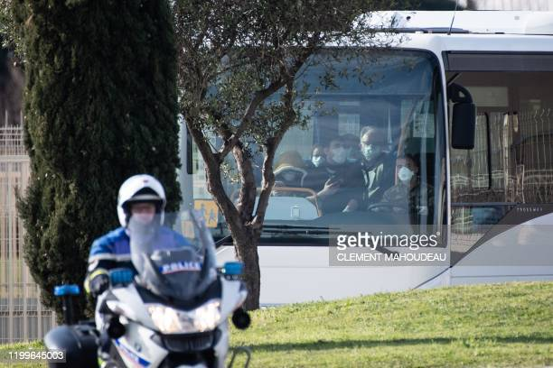 A police officer escort the bus carry people disembarked from an aircraft at the IstresLe Tube Air Base near Istres northwest of Marseille southern...