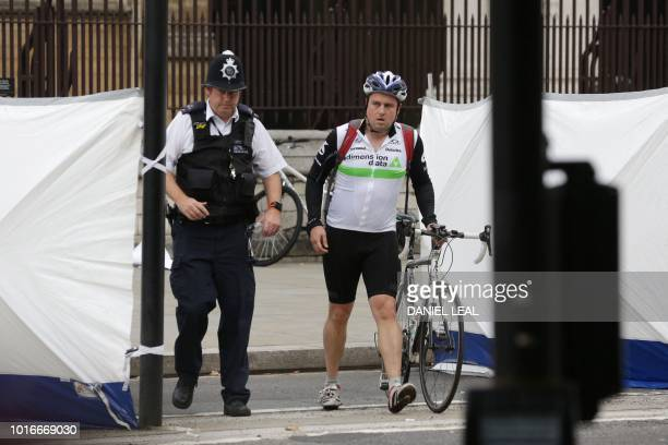 A police officer escorts a cyclist out of the exclusion zone at the Houses of Parliament in central London following an incident this morning where a...