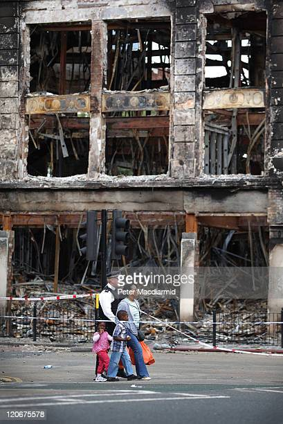 A police officer escorts a family past a burnt out Carpetright shop in Tottenham on August 8 2011 in London England Pockets of rioting and looting...