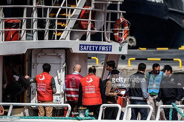 A police officer escorts a migrant deported from Greece after he arrived aboard a small Turkish ferry in the port of Dikili district in Izmir Turkey...