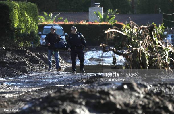 A police officer escorts a resident through a neighborhood that was destroyed by a mudslide on January 12 2018 in Montecito California 17 people have...