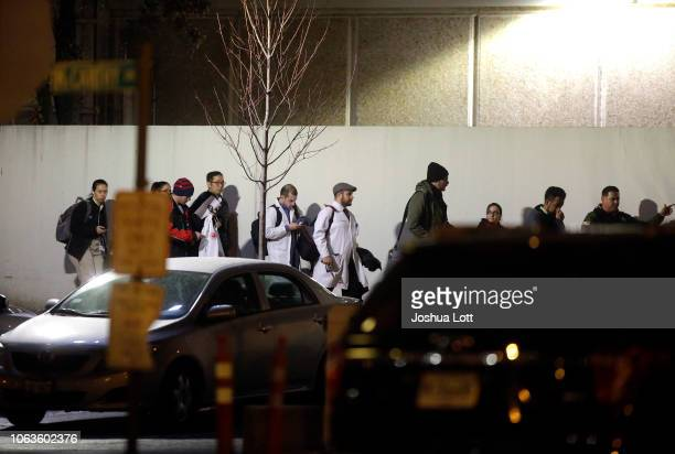 A police officer escorts Mercy Hospital workers to the main entrance after a gunman shot multiple people on November 19 2018 in Chicago Illinois...