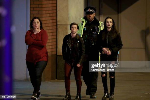 A police officer escorts people near to Manchester Arena on May 23 2017 in Manchester England An explosion occurred at Manchester Arena as concert...