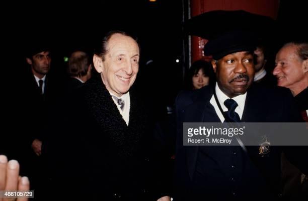 Police officer escorts Russian-born American pianist Vladimir Horowitz into Carnegie Hall, January 8, 1978.