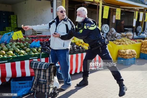 Police officer evacuates a shopper from The Hague market, one of the largest market in Europe, amid the worsening COVID-19 virus pandemic on March...
