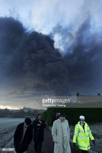 A police officer evacuates residents near plumes of smoke rising from Bruncefield oil depot on December 11 2005 in Hemel Hempstead EnglandThe...