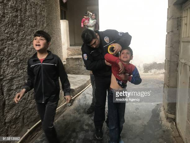 A police officer examines a wounded boy after rockets launched by PYD/PKK terrorists from Syria's Afrin hit a house and a street in Reyhanli district...
