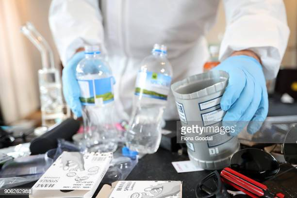 A police officer examines chemicals and equipment found in a methamphetamine manufacturing lab following a police raid on January 17 2018 in Auckland...