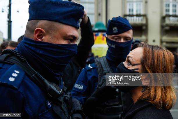 Police officer faces a woman in mask as she argues against a pro life counter protest during the fourth day of protests against the Constitutional...