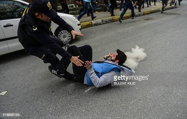 A police officer fights with a Kurdish man while people run away as Turkish riot policemen use rubber bullet to prevent people from gathering for...