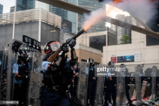 A police officer fire teargas during a protest on June 12 2019 in Hong Kong China Large crowds of protesters gathered in central Hong Kong as the...