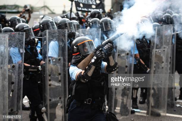 TOPSHOT A police officer fires tear gas during clashes with protesters during a rally against a controversial extradition law proposal outside the...