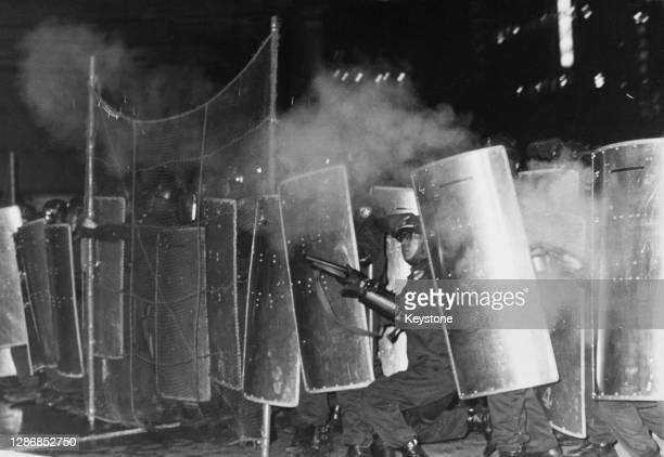 Police officer fires tear gas from the shelter of officers with shields and wire netting to protect them from rocks being thrown by rioting student...