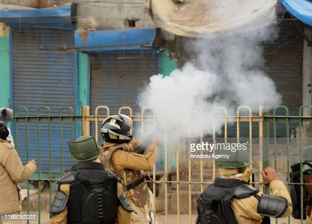 Police officer fires tear gas towards demonstrators during a protest against a new citizenship law in Seelampur area of Delhi, India on December 17,...