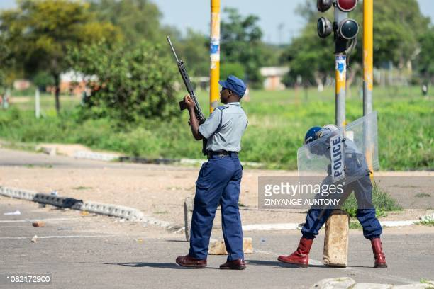 A police officer fires warning shot to disperse protesters during a stayaway demonstration against the doubling of fuel prices on January 14 2019 in...