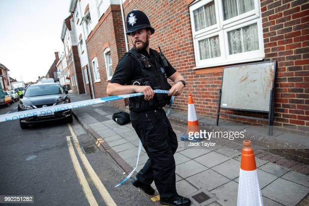 A police officer fixes police tape across a street by a supported housing project in Salisbury after a major incident was declared when a man and...