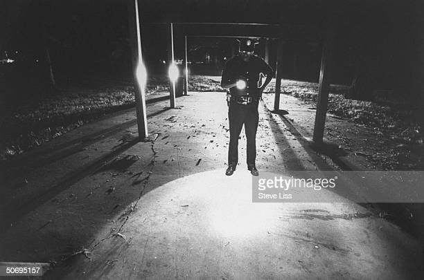 Police officer flashlightilluminating site where 3 white Highland Township trainhopping teens were allegedly assaulted by local black youths in...