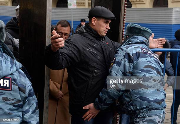 A police officer frisks a visitor's at the Red square in central Moscow on December 31 2013 as security measures were increased in Russian capital...