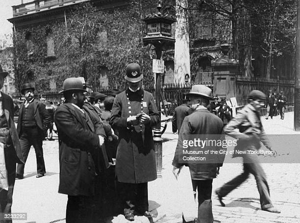 A police officer from the Broadway Squad gives directions to some men on the corner of Fulton Street and Broadway in New York City