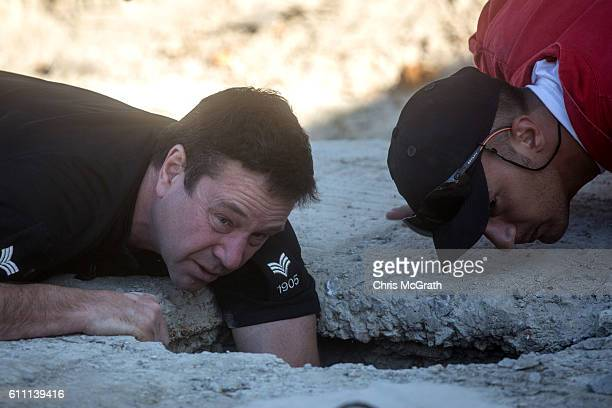 A police officer from the South Yorkshire Police and a member of the Greek rescue service look inside a hole cut into a septic tank during the...