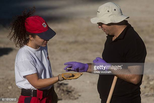 A police officer from the South Yorkshire Police and a member of the Greek rescue service examine an item found at the excavation site of missing...