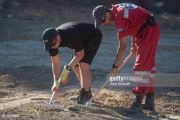 A police officer from the South Yorkshire Police and a member of the Greek rescue service rake through soil at the excavation site of missing toddler...