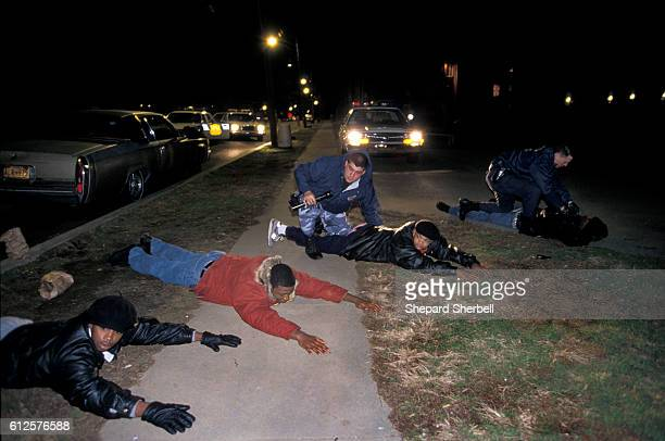 A police officer from Violent Crime Response Team of Washington DC Metropolitan Police holds down young men suspected of selling crack cocaine
