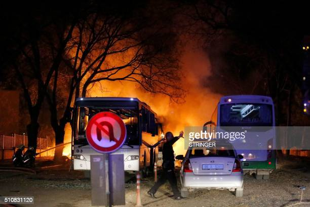 A police officer gestures as he walks at the site of an explosion while firefighters try to extinguish flames after an attack targeted a convoy of...
