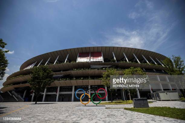 Police officer gestures as he walks in front of the Olympic Stadium in Tokyo on July 20, 2021 ahead of the Tokyo 2020 Olympic Games.