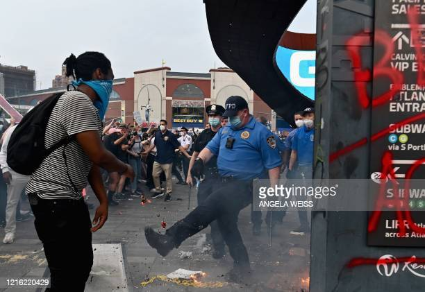A police officer gestures near a small fire burning as protesters gather for a Black Lives Matter protest near Barclays Center on May 29 2020 in the...