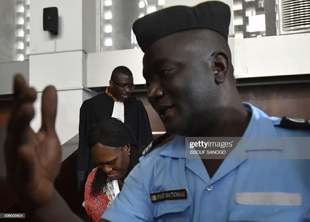 A police officer gestures next to Ivory Coast's former first lady Simone Gbagbo (C) at the appeal court of Abidjan on May 31, 2016. Simone Gbagbo goes on trial for crimes against humanity in what many see as a litmus case for justice in the West African country. The hearings into the 66-year-old's role in post-election carnage in 2010 is expected to last a month with 32 witnesses testifying. / AFP / ISSOUF