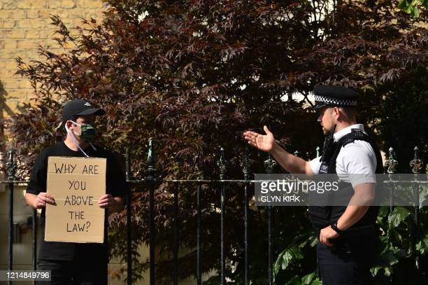 A police officer gestures to move on a demonstrator holding a placard that reads Why are you above the law protests outside the home of Number 10...