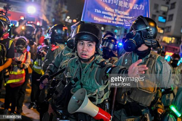 Police officer gestures towards the media during a protest at Hung Hom in Hong Kong on December 1, 2019. - Police fired tear gas and pepper spray in...