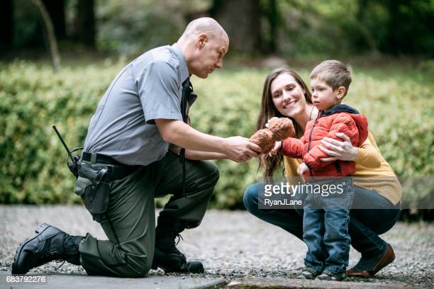 police officer giving child stuffed animal - forze di polizia foto e immagini stock