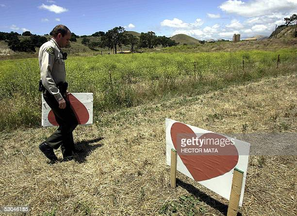 Police officer grabs a sign that was remove by a car on the road to Pop icon Michael Jackson's Neverland Ranch in Los Olivos, CA 09 June 2005. Police...