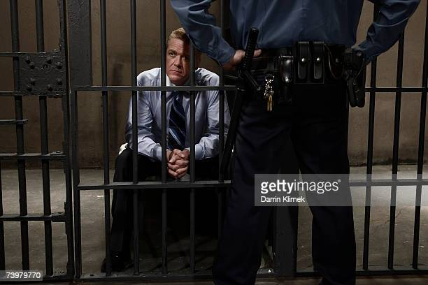 police officer guarding man in prison cell, rear view, mid section - defending stock photos and pictures