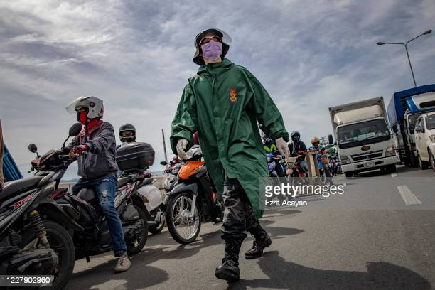 Police officer guards a quarantine checkpoint on the first day of a reimposed lockdown to curb the spread of COVID-19, on August 4, 2020 in Quezon...