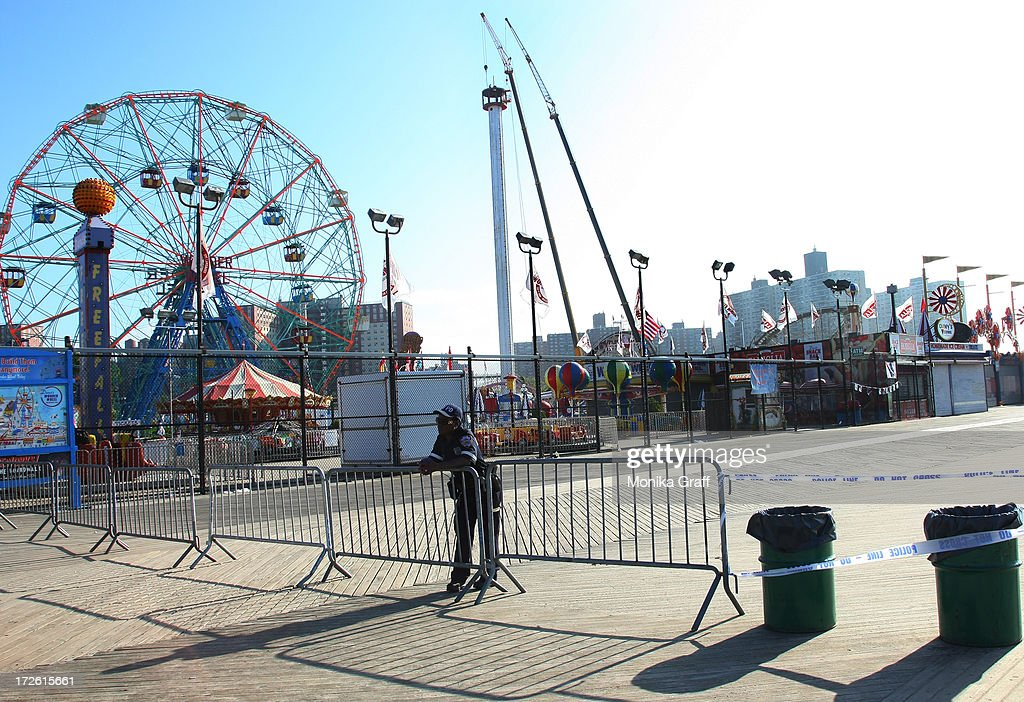 A police officer guards a section of the boardwalk which is closed off to the public as the Astrotower, far right, is disassembled in Coney Island on July 4, 2013 in the borough of Brooklyn in New York City. Officials decided to close Luna Park and sections of the boardwalk while workers take down the amusement tower which was seen precariously swaying two days ago.