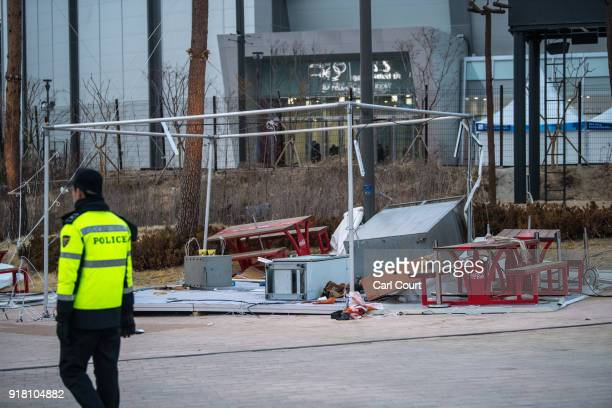 A police officer guards a temporary structure blown over during high winds in the Gangneung Coastal Cluster during the PyeongChang Winter Olympics on...