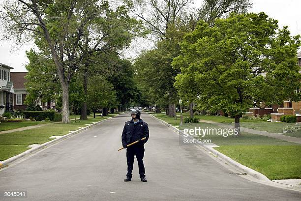 A police officer guards deserted streets prior to the start of a Ku Klux Klan rally May 31 2003 in west suburban Chicago town of Berwyn Illinois An...