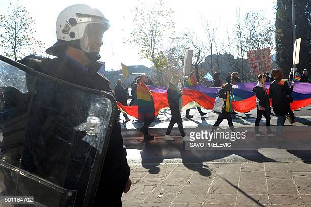 A police officer guards Montenegrin gay activists during a Gay Pride parade in Podgorica on December 13 2015 Some hundred people marched in Podgorica...