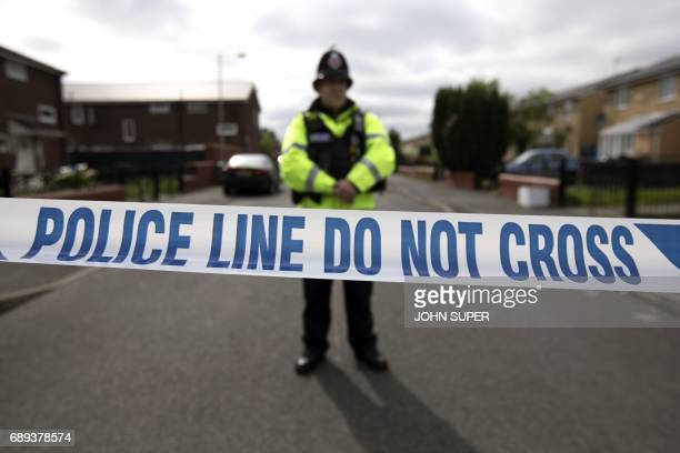 TOPSHOT A police officer guards the entrance to a street in the Moss Side area of Manchester on May 28 2017 during an operation A British minister...