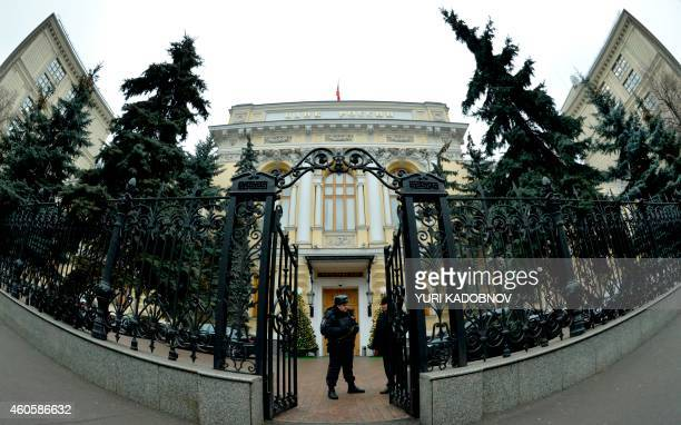 A police officer guards the entrance to the head office of the Central Bank in Moscow on December 17 2014 Russia scrambled on December 17 2014 to...