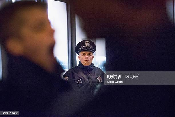 Police officer guards the front of Chicago police headquarters during a prayer vigil and demonstration called to protest the death and subsequent...
