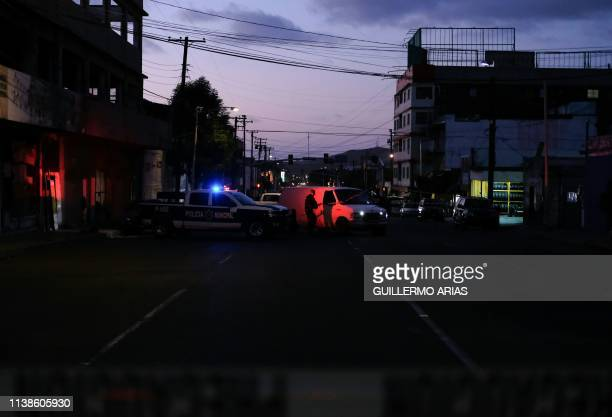 A Police officer guides the forensic van inside the perimeter of the scene of a crime where a man was killed by gun fire in downtown Tijuana Baja...