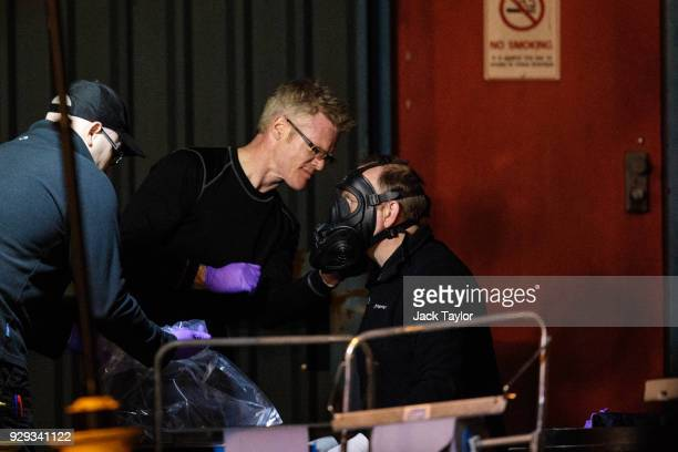 A police officer has a protective mask removed on an industrial site during investigations into the poisoning of Sergei Skripal in Salisbury who was...